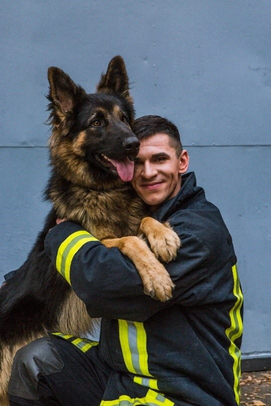 Fireman and dog hugging each other
