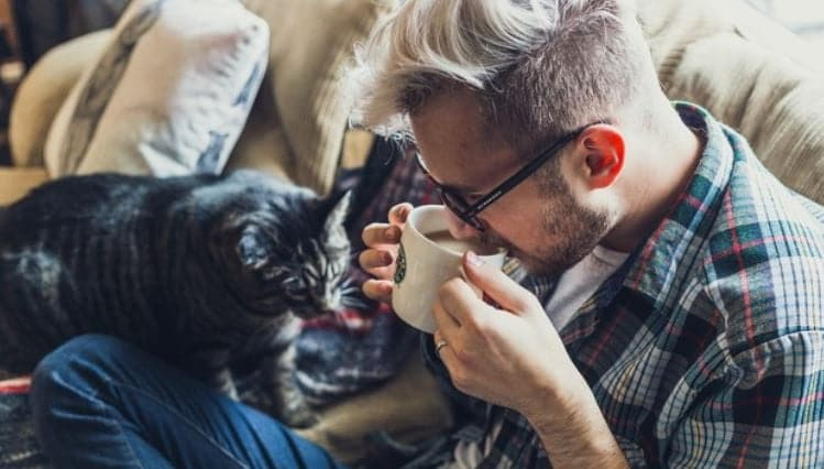 Man drinking coffee on the couch with cat